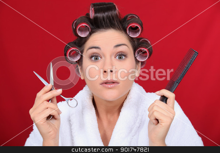 Woman with her hair in curlers holding scissors and a comb stock photo, Woman with her hair in curlers holding scissors and a comb by photography33