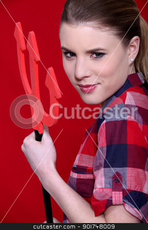 A cute woman holding the evil pitchfork. stock photo, A cute woman holding the evil pitchfork. by photography33
