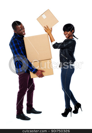 Smiling couple moving cardboard boxes stock photo, Man holding pile of cardboard boxes as woman places them one at a time by Ishay Botbol