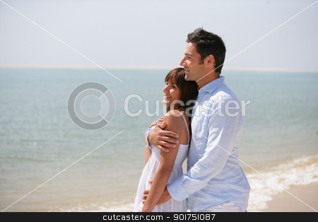 Couple standing on a beach stock photo, Couple standing on a beach by photography33