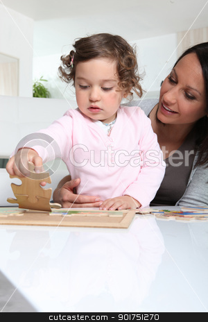 Mother and daughter doing a jigsaw puzzle stock photo, Mother and daughter doing a jigsaw puzzle by photography33