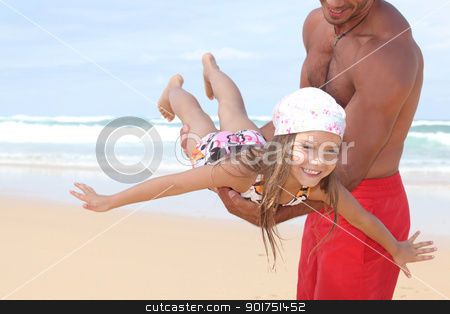 Man flying his daughter around a beach stock photo, Man flying his daughter around a beach by photography33