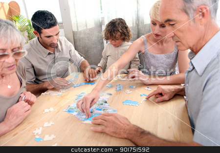 Family completing jigsaw together stock photo, Family completing jigsaw together by photography33