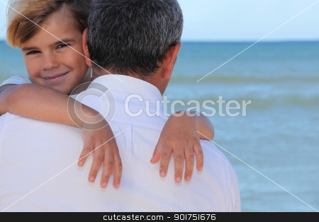 A father hugging his son on the beach. stock photo, A father hugging his son on the beach. by photography33