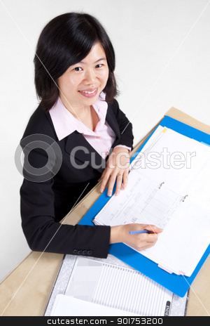 Businesswoman signing document. stock photo, A businesswoman sitting at the table with document. by szefei