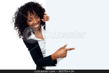 Female representative pointing towards placard stock photo, Female representative pointing towards placard and smiling at camera by Ishay Botbol