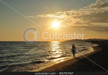 Sunset on beach stock photo, Walking on sandy sea beach at sunset by zagart