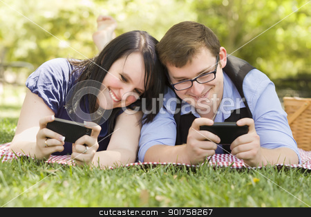 Young Couple at Park Texting Together stock photo, Attractive Young Couple at the Park Texting on Their Smart Phones Together. by Andy Dean