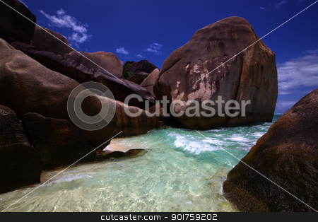 Clear ocean water washes in among shore rocks stock photo, Clear ocean water washes in among weathered shore rocks worn smooth from years of waves by Damian Chrascina