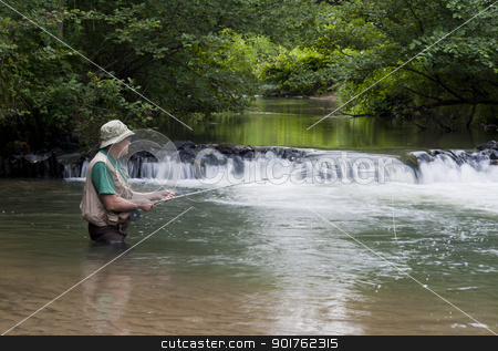 trout fisherman stock photo, man fishing for trout next to a small waterfall by digitalreflections