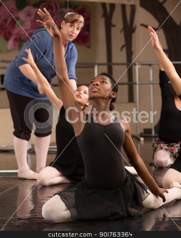 Kneeling Dance Students stock photo, Ballet class teacher helps students practice dance moves by Scott Griessel