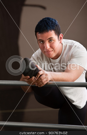Happy Dancer Stretching stock photo, Smiling young male dancer stretching for practice by Scott Griessel