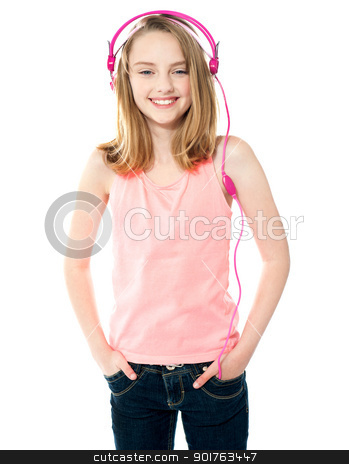 Pretty girl enjoying music through headphones stock photo, Pretty trendy girl listening to music through headphones and posing in style by Ishay Botbol