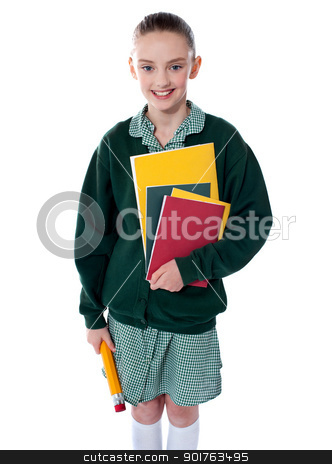 School girl standing with notebooks stock photo, School girl standing with notebooks and pencil by Ishay Botbol