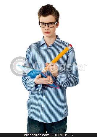 A boy writing on spiral notebook stock photo, A boy writing on spiral notebook with large pencil. Serious look on face by Ishay Botbol