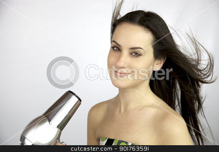 Young female model blow drying her long silky hair stock photo, Happy woman smiling while blowdryer send air on her long hair by federico marsicano