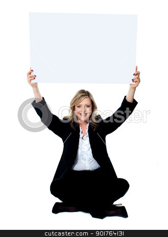 Seated female employee holding white clipboard over her head stock photo, Female employee sitting with crossed legs holding white clipboard over her head by Ishay Botbol
