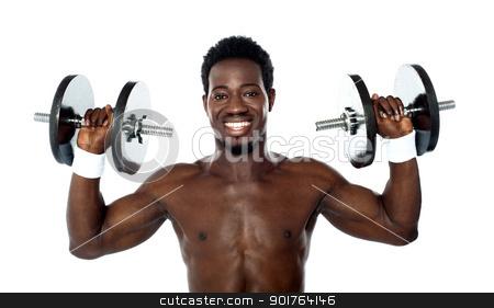 Male athlete holding dumbbells stock photo, Male athlete holding dumbbells above his shoulders by Ishay Botbol