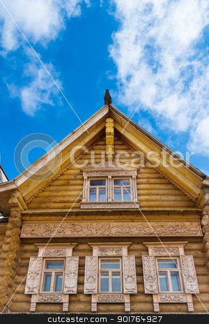 Wooden decorated windows stock photo, Wooden decorated windows in log house under blue sky, Russian traditional architecture. by Iryna Rasko