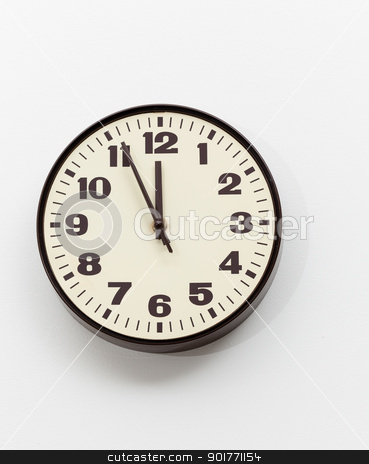 Brown clock on white office wall near noon stock photo, Brown simple plastic wall clock on the wall of office and concept of running out of time by Steven Heap