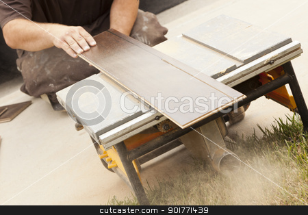 Contractor Using Circular Saw Cutting of New Laminate Flooring stock photo, Contractor Using Circular Saw Cutting of New Laminate Flooring Renovation. by Andy Dean