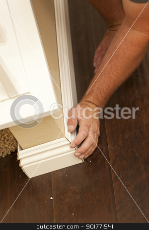 Contractor Fitting New Baseboard to Wall and New Laminate Floori stock photo, Contractor Fitting New Baseboard to Wall and New Laminate Flooring Abstract. by Andy Dean