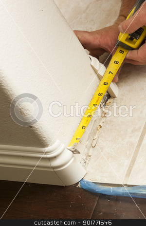 Measuring for New Baseboard with Bull Nose Corners and New Lamin stock photo, Contractor Measuring for New Baseboard with Bull Nose Corners and New Laminate Flooring Abstract. by Andy Dean
