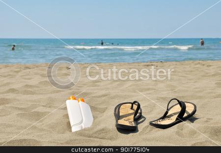 Slippers on beach stock photo, Female slippers and sun cream on beach stock photo by zagart
