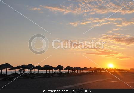 Sunset on beach stock photo, Umbrella on sandy sea beach at sunset stock photo by zagart