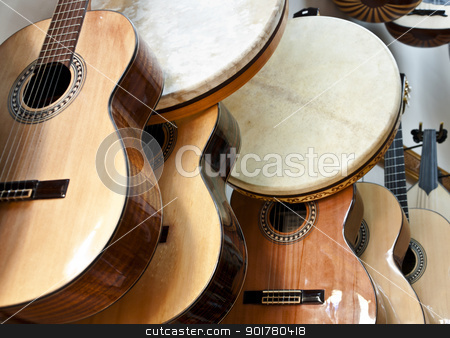Guitars and bendirs stock photo, Acoustic guitars and bendirs hanging on a wall in a music shop by HypnoCreative