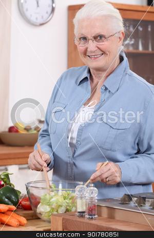 Senior woman preparing salad stock photo, Senior woman preparing salad by photography33