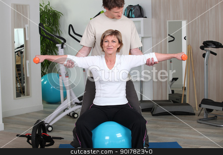 Woman in the gym with instructor stock photo, Woman in the gym with instructor by photography33