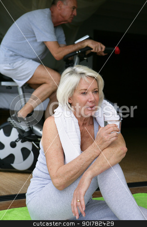 Woman drinking a glass of water during a workout stock photo, Woman drinking a glass of water during a workout by photography33