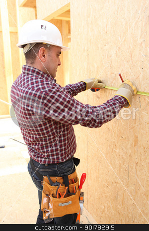 A carpenter taking measures onsite. stock photo, A carpenter taking measures onsite. by photography33