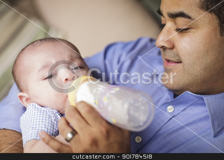 Happy Hispanic Father Bottle Feeding His Son stock photo, Happy Hispanic Father Bottle Feeding His Very Content Son. by Andy Dean