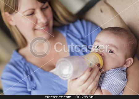 Happy Mother Bottle Feeding Her Son stock photo, Happy Mother Bottle Feeding Her Very Content Son. by Andy Dean
