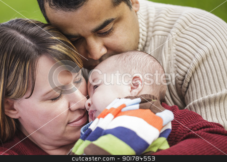 Happy Mixed Race Parents Hugging Their Son stock photo, Happy Mixed Race Parents Hugging Their Son in the Park. by Andy Dean