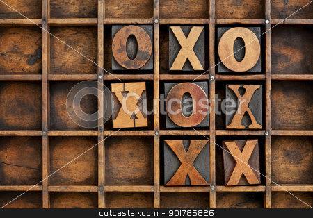 tic-tac-toe or noughts and crosses  stock photo, tic-tac-toe or noughts and crosses game - vintage letterpress printing block X and O in wooden grunge typesetter box with dividers by Marek Uliasz