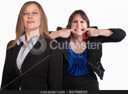 Angry Woman Makes a Face stock photo, Angry woman makes face behind person over white by Scott Griessel