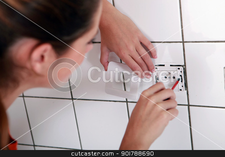 Woman fixing an outlet stock photo, Woman fixing an outlet by photography33
