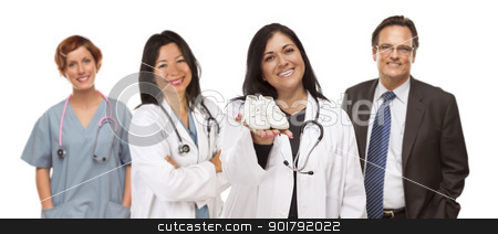 Hispanic Female Doctor or Nurse with Baby Shoes and Support Staf stock photo, Attractive Hispanic Female Doctor or Nurse Holding Out Baby Shoes and Support Staff Behind Isolated on a White Background. by Andy Dean