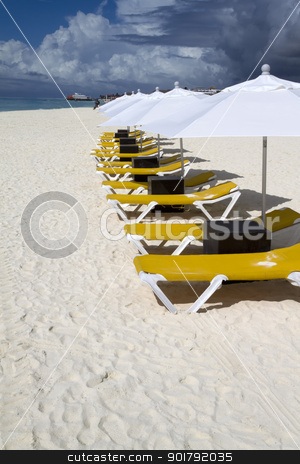 Row of Lunge Chairs and Umbrellas stock photo, Rows of several lounge chairs and umbrellas on the beach by Kevin Tietz
