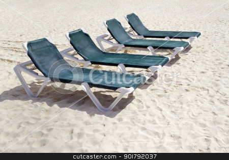 Green Beach Chairs stock photo, Rows of several green lounge chairs on the beach by Kevin Tietz