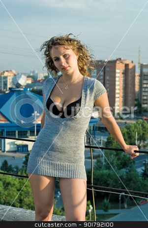 Pretty girl on roof stock photo, Young beautiful woman standing on roof at city background by Aikon