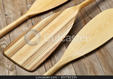 wooden canoe paddles stock photo, blades of three wooden canoe paddles of different shape against grunge wood surface by Marek Uliasz