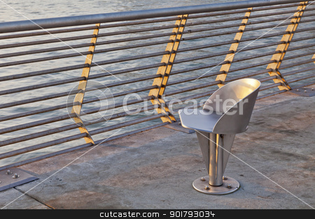 metal chair at waterfornt stock photo, modern outdoor metal swivel chair at sunrise - San Francisco waterfront Pier 14 by Marek Uliasz