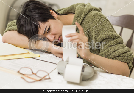 Mixed Race Young Female Agonizing Over Financial Calculations stock photo, Mixed Race Young Female Agonizing Over Financial Calculations in Her Kitchen. by Andy Dean