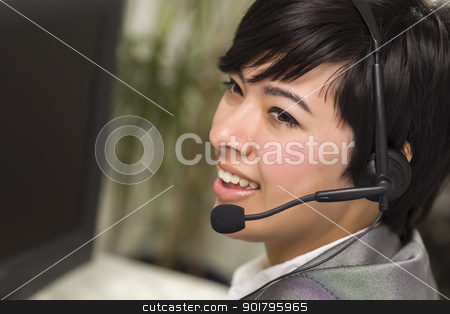 Attractive Young Mixed Race Woman Smiles Wearing Headset stock photo, Attractive Young Mixed Race Woman Smiles Wearing Headset Near Computer Monitor. by Andy Dean