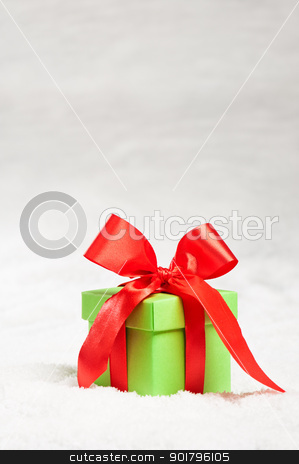 Green present with red ribbon over snow stock photo, Green present with red ribbon over snow, over white by Ulrich Schade