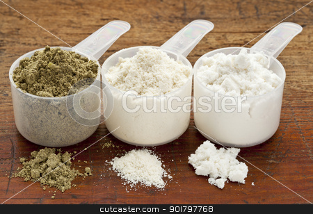 hemp and whey protein powder stock photo, plastic measuring scoops of three protein powders (from left hemp seed, whey concentrate, whey isolate) on a grunge wood surface by Marek Uliasz